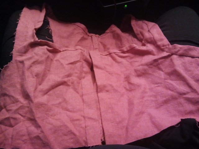 top of a pink dress with the neckline bound in a narrow hem tape and the center front opening bound in a wider hem tape