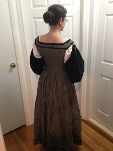 me facing away showing the back of grey dress with gathered skirt and square neck and black velvet sleeves