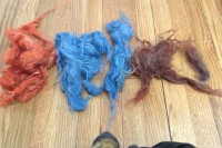 5 piles of wool locks dyed red-orange, blue, and purple/red/brown, I don't know what to call it