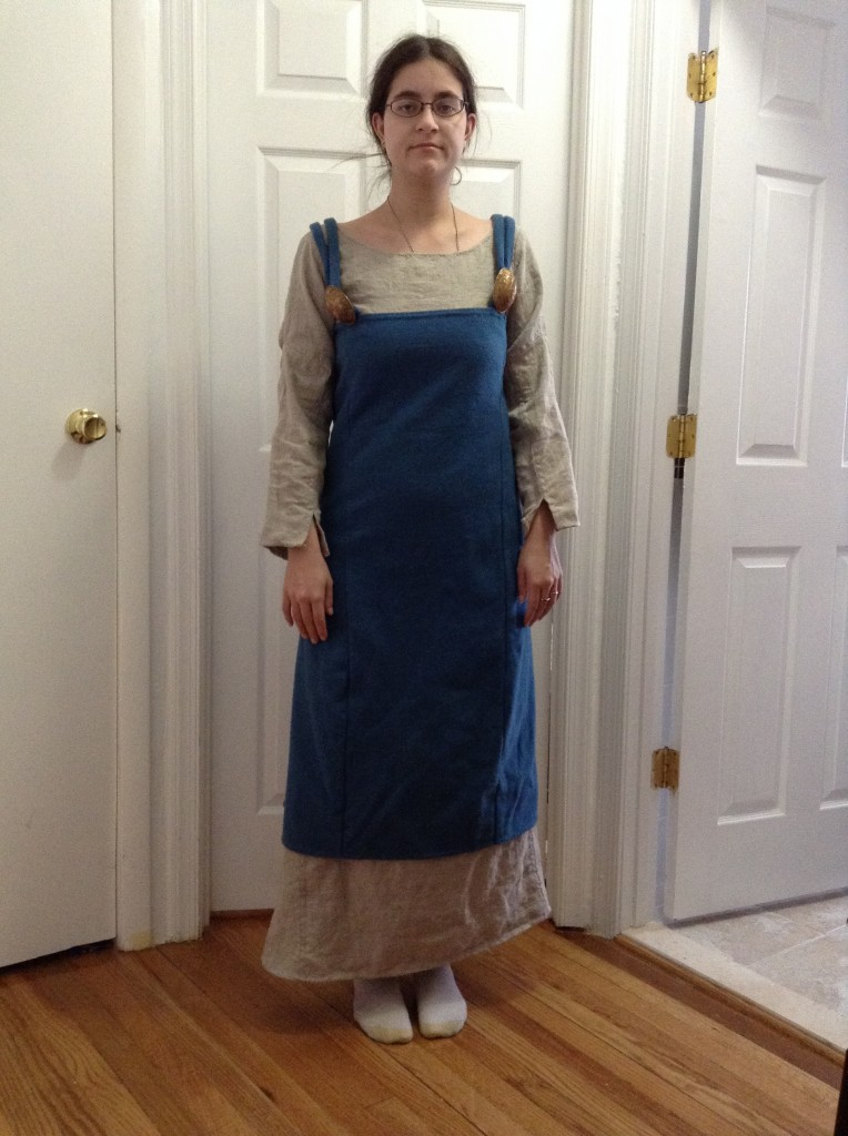 I stand wearing an unbleached linen long-sleeve underdress and a blue wool apron dress