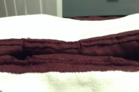 view of the inside of the waist, where single and triple box pleats are whip stitched to the bodice. Burgundy wool with dark red silk stitches.