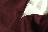 burgundy fabric on a white background revealing two hemmed edges reinforced with a buttonhole bar of dark red silk